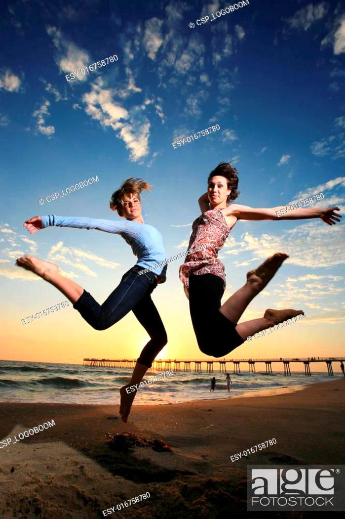 Stock Photo: Happy girls jumping at the beach at sunset.