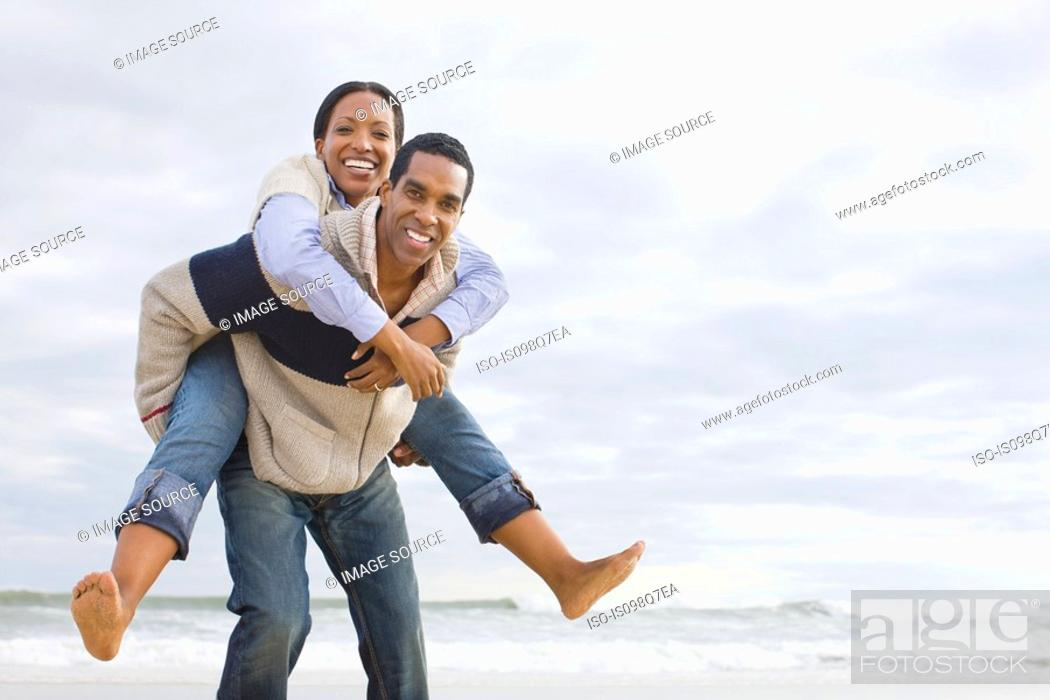 Stock Photo: Man giving woman piggyback by the sea.