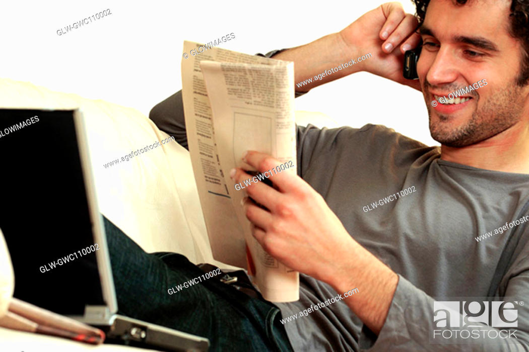 Stock Photo: Close-up of a young man reading a newspaper and talking on a mobile phone.