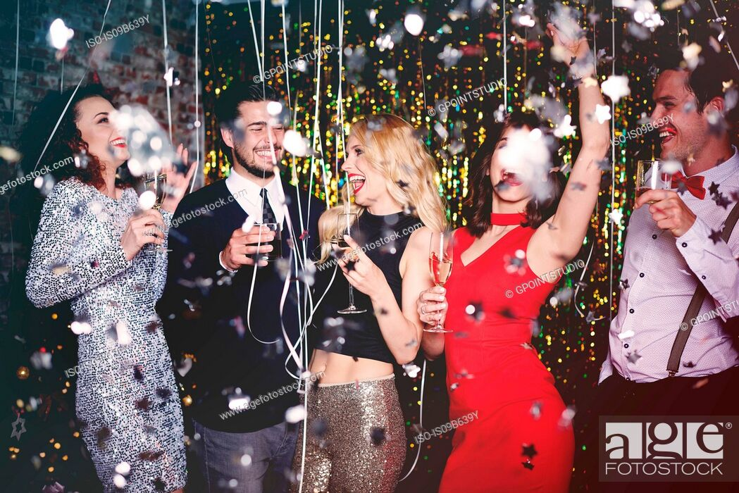 Photo de stock: Group of people dancing and having fun at party, glitter falling through air.