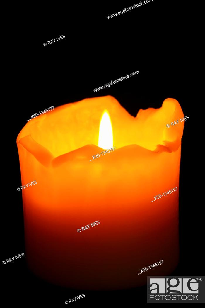 Stock Photo: A burning, well used candle with ragged melting edges against a dark background  Isolated.