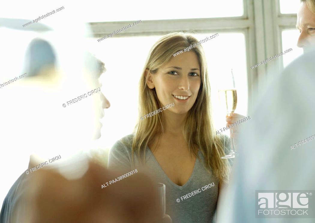 Stock Photo: Young woman holding up glass of champagne during office party.