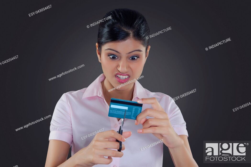 Stock Photo: Businesswoman cutting credit card with scissors.