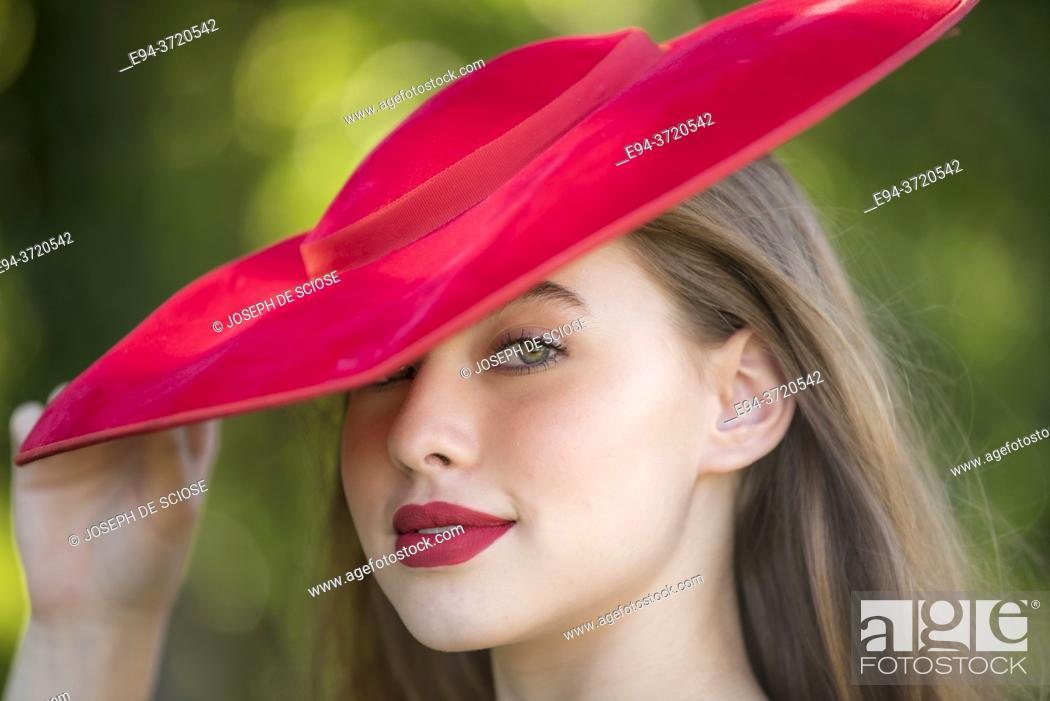 Stock Photo: A 15 year old girl wearing a red hat looking directly at the camera.