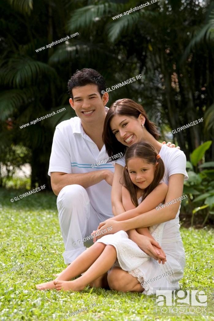 Stock Photo: Portrait of a young couple with their daughter sitting in a garden.