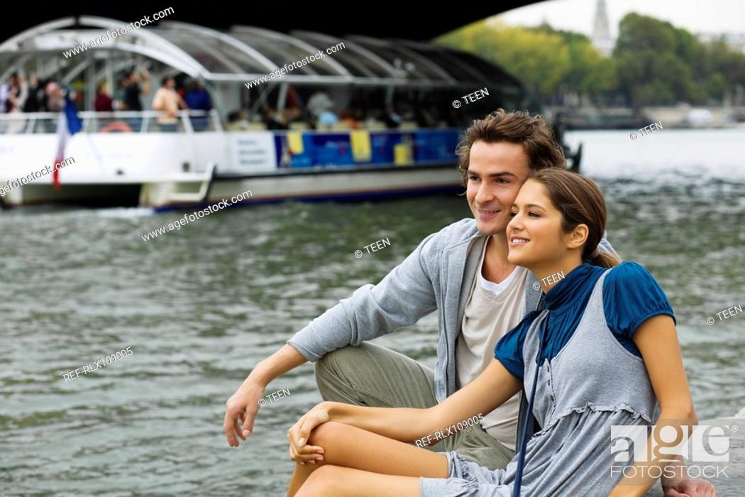 Stock Photo: Young couple sitting by river Seine watching tourist boats, Paris France.