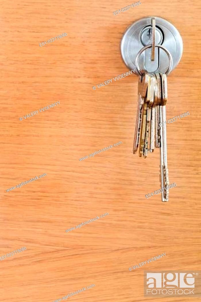 Photo de stock: bunch of home keys in lock of wood door.