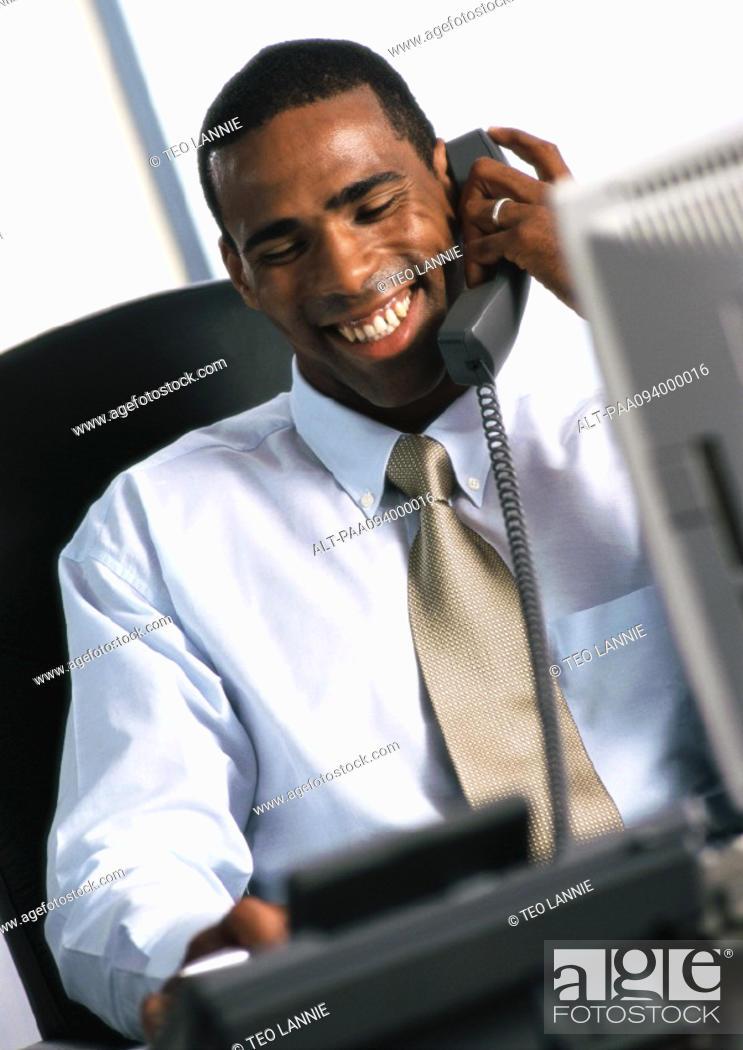 Stock Photo: Businessman using telephone, smiling.