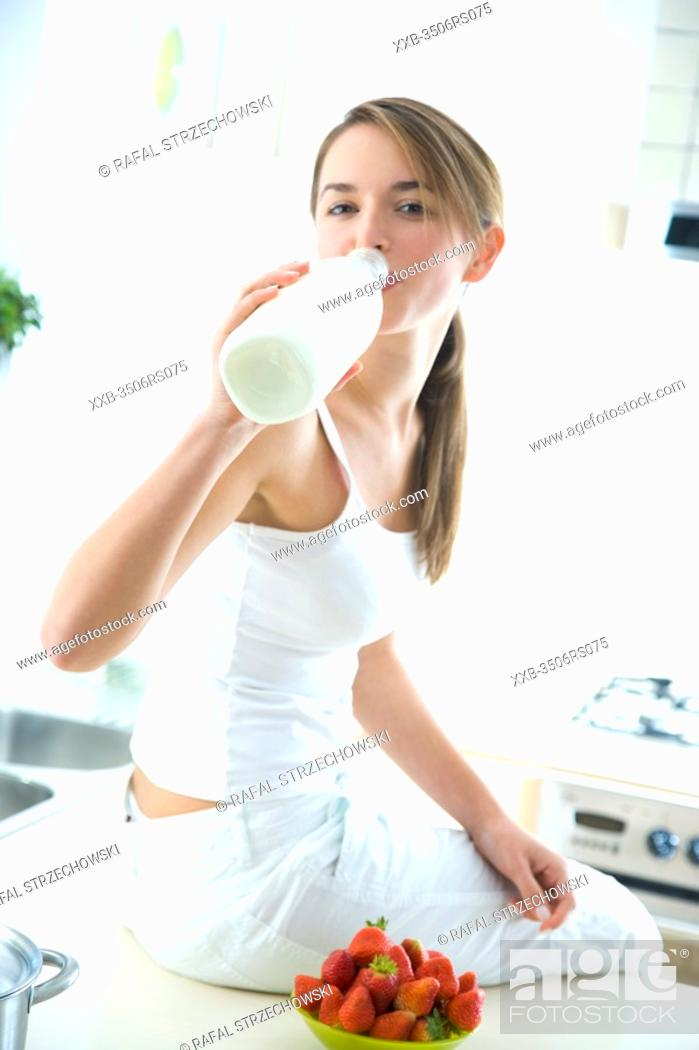 Stock Photo: woman drinking milk in kitchen.