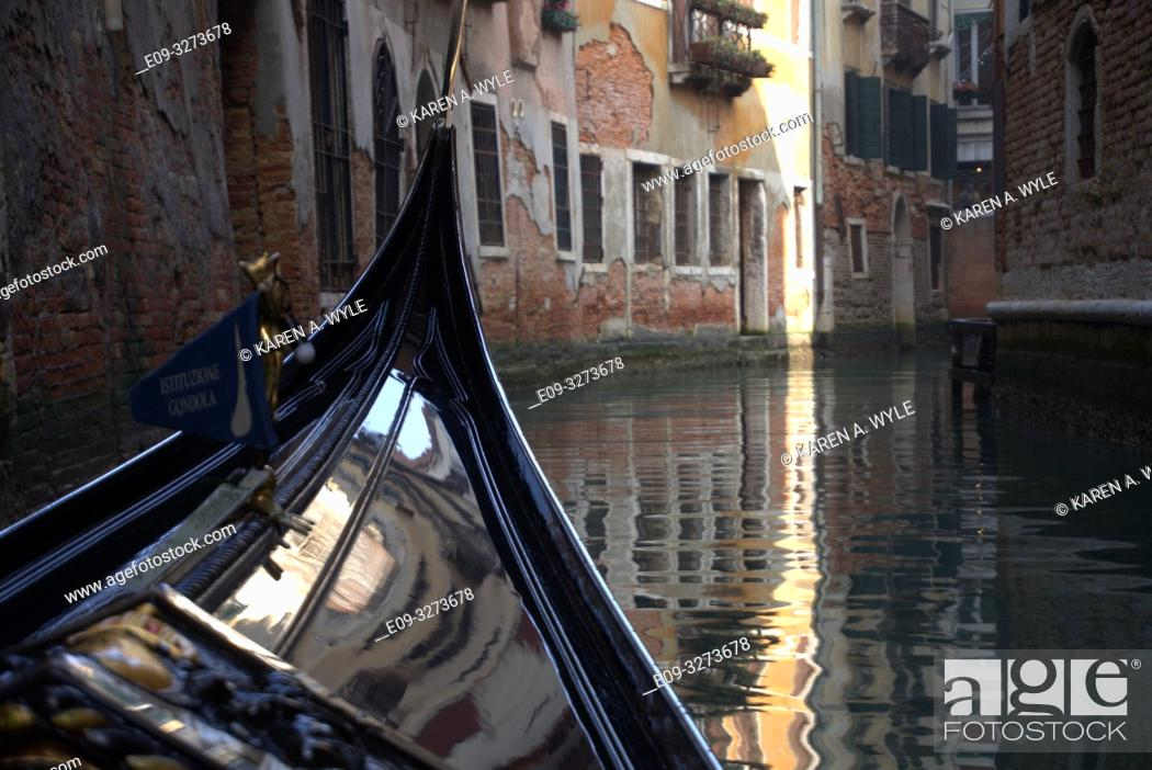 Stock Photo: view from gondola on canal in Venice, Italy, bend up ahead, peeling building walls, shaft of light on building and reflected in water.