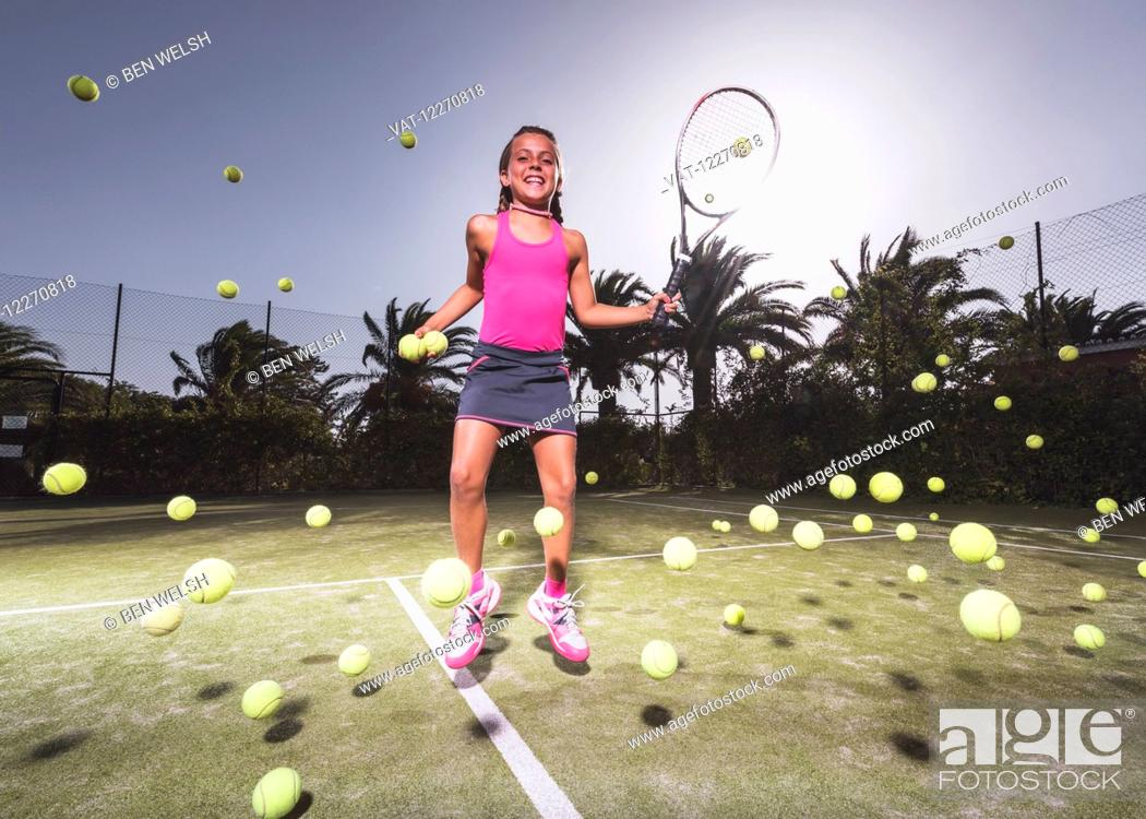 Imagen: A teenage girl on a tennis court with a racquet and numerous tennis balls; Tarifa, Cadiz, Andalusia, Spain.