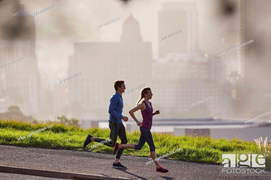 Stock Photo: Runner couple running on sunny urban city sidewalk.