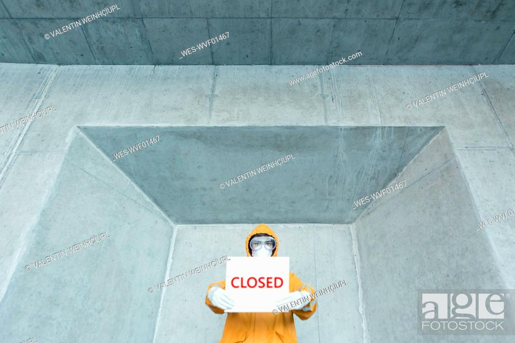 Stock Photo: Portrait of man wearing protective clothing holding a 'closed' sign.