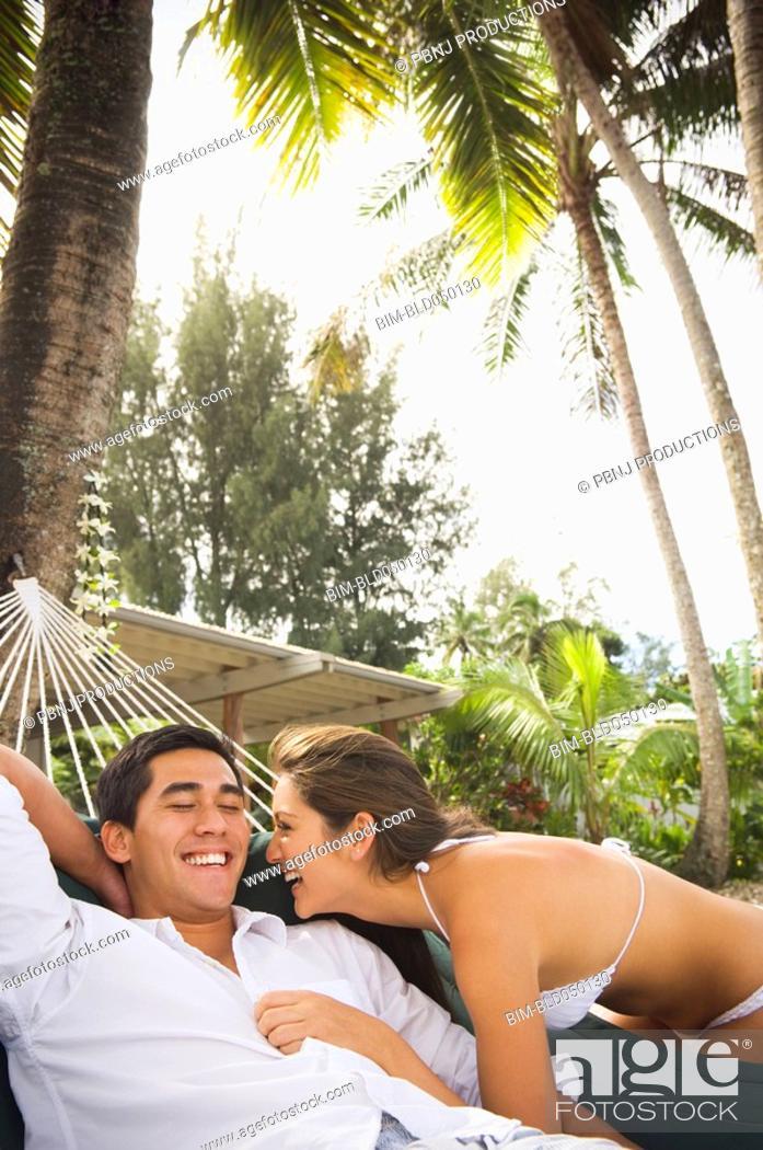 Stock Photo: Multi-ethnic couple laughing on beach.
