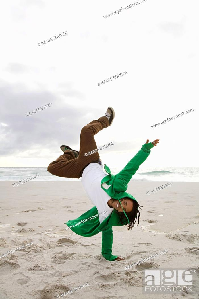 Stock Photo: Young man doing cartwheels on beach.