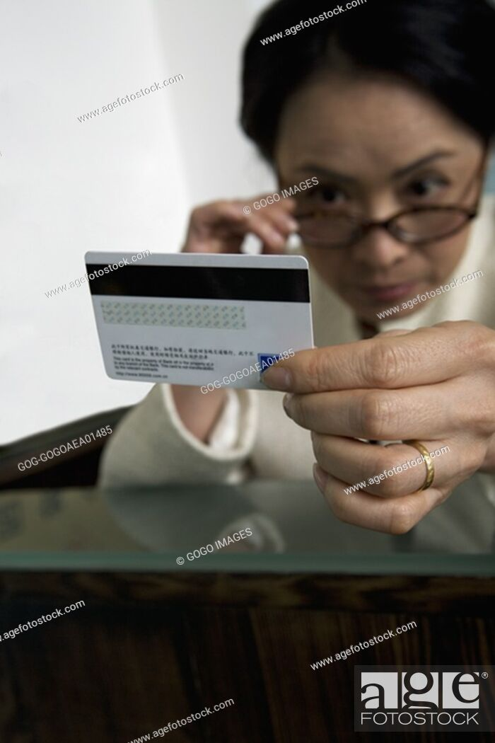Stock Photo: Woman examining credit card.