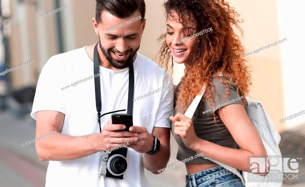 Stock Photo: Happy couple visiting city in summertime and looking photos.