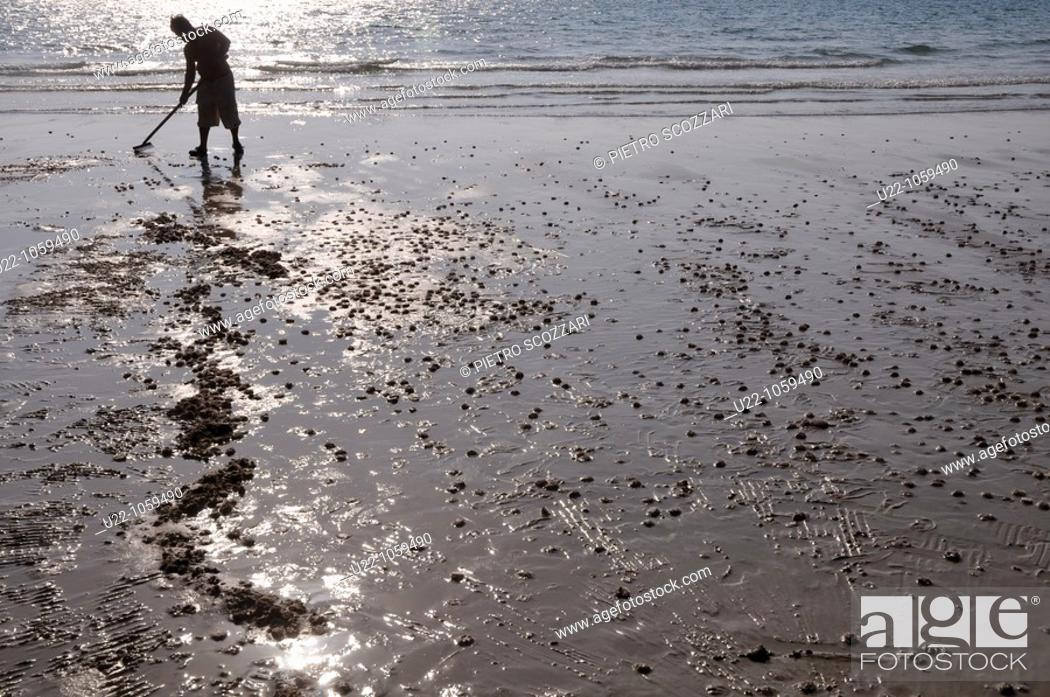 Stock Photo: Sihanoukville (Cambodia): a man cleaning the beachfront at Otras Beach.