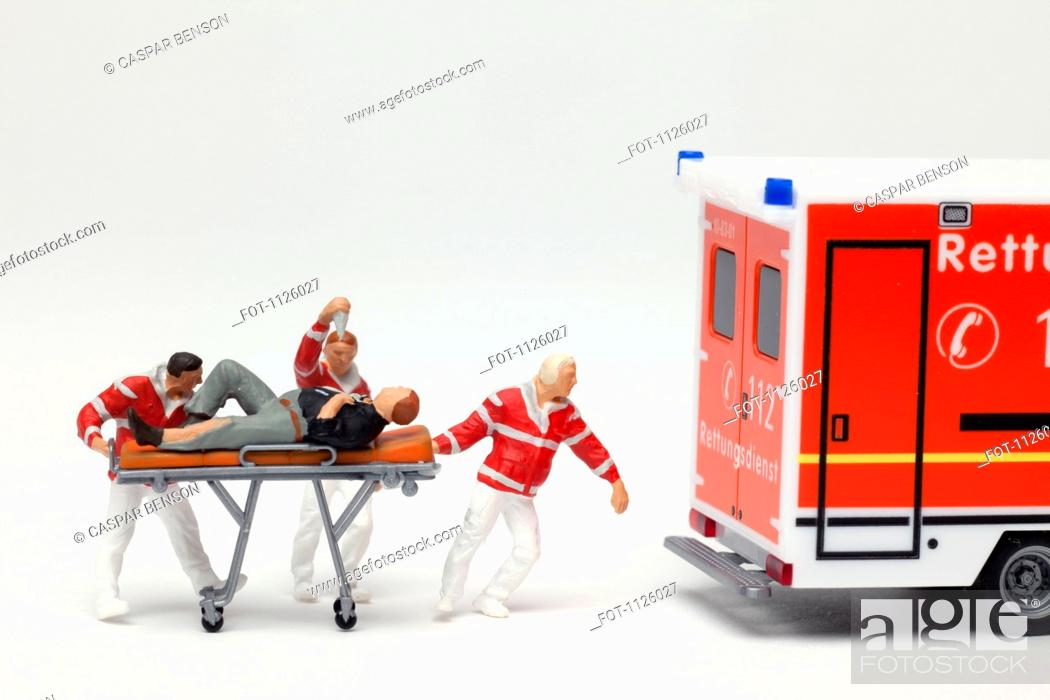 Stock Photo: Miniature EMT figurines wheeling a patient on a gurney to a toy ambulance.