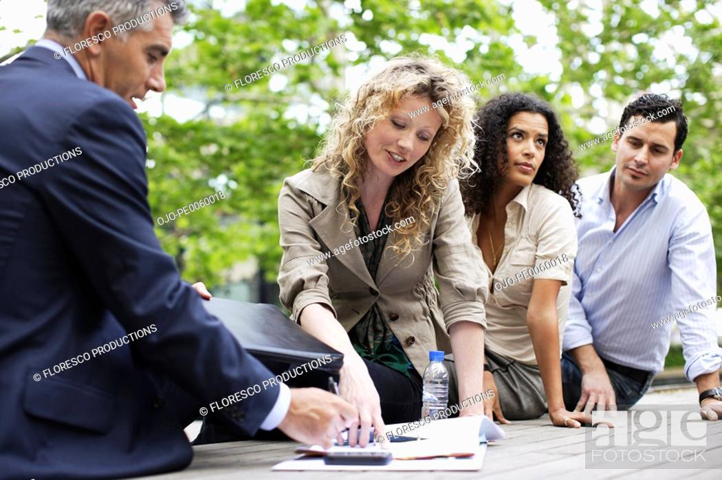 Stock Photo: Four businesspeople outdoors on deck with paperwork.