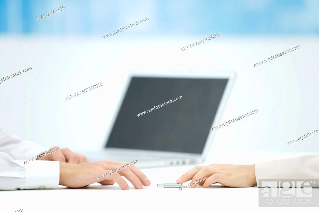 Stock Photo: Hand pushing a flash drive across desk to another hand reaching for it.