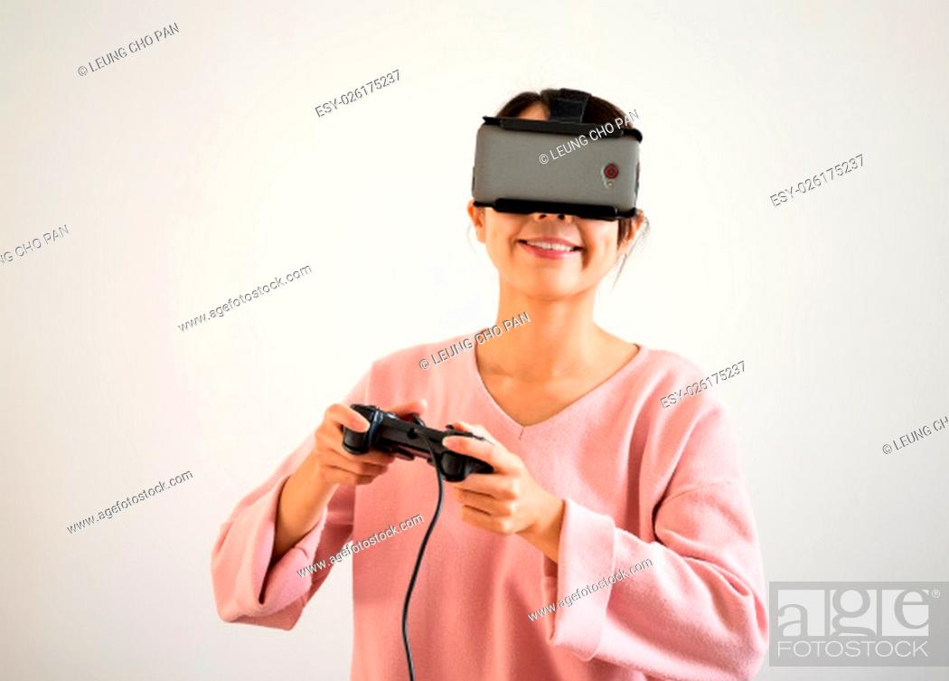 Stock Photo: Woman play tv game on joystick and vr device.