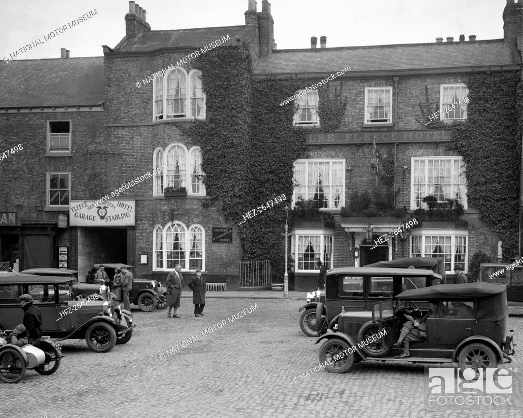 Stock Photo: Cars parked outside the Fleece Hotel, Thirsk, Yorkshire, Ilkley & District Motor Club Trial, 1930s. Artist: Bill Brunell.