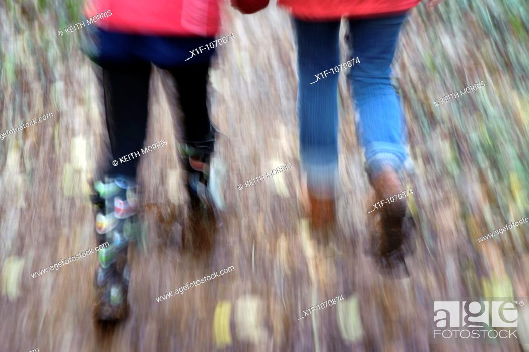 Stock Photo: A mother and her daughter walking in autumn woodland Pembrokeshire Wales UK.