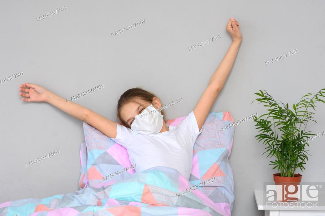 Stock Photo: A recovering girl in a medical mask woke up in the morning and stretches herself in bed.