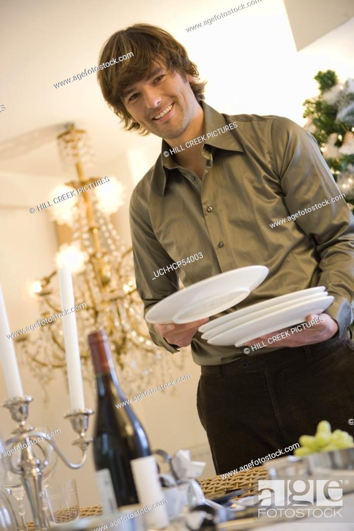Stock Photo: Man setting dinner table.