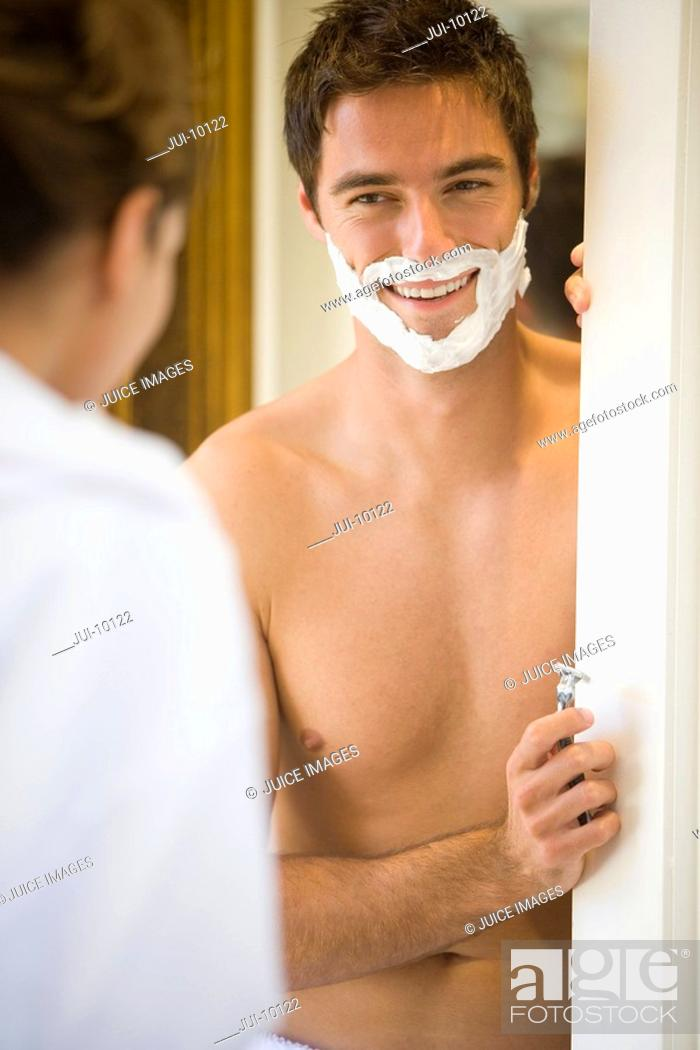 Stock Photo: Man preparing to shave, smiling at woman differential focus.