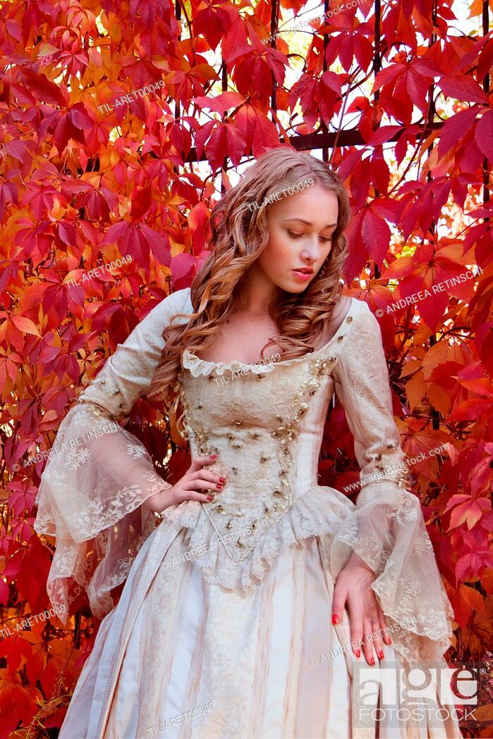 Stock Photo: Blonde young woman in period costume standing outdoors beside red autumn leaves.