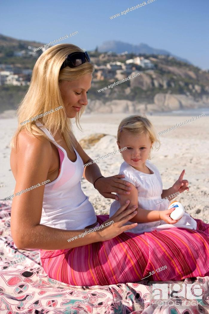 Stock Photo: Mother applying sunscreen to baby girl 12-15 months on beach, side view.