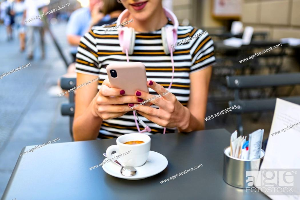 Stock Photo: Young woman using smartphone at pavement cafe, partial view.