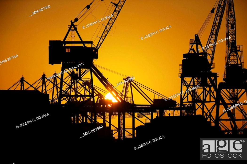 Stock Photo: Sunrise through loading cranes, Los Angeles Harbor, California, USA.
