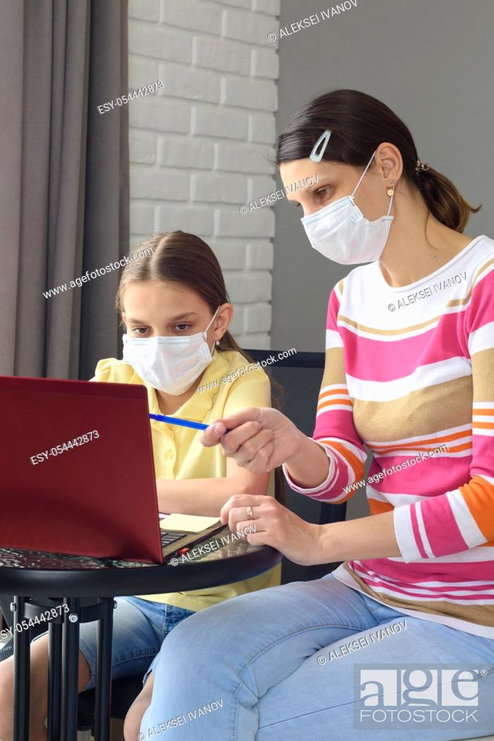 Stock Photo: The girl helps the child to do quarantine lessons.