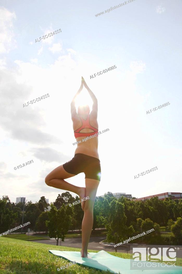 Stock Photo: Young Woman doing the tree pose on mat.