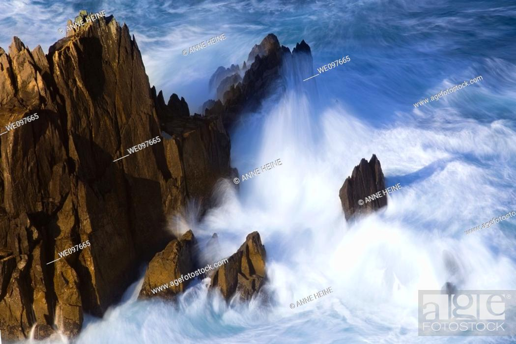 Stock Photo: long exposure of ocean surf splashing against rock,.