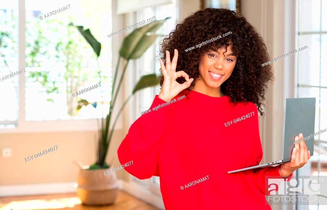Imagen: African american woman standing using computer laptop at home doing ok sign with fingers, excellent symbol.