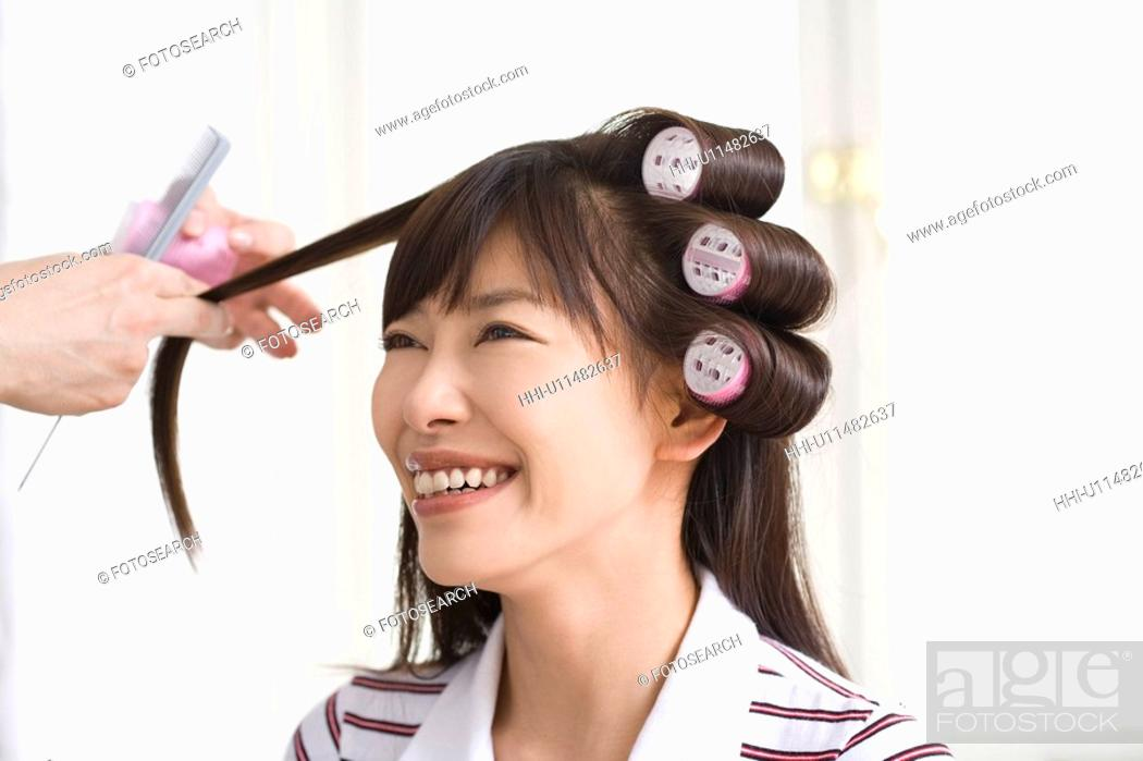 Stock Photo: Hairdresser cutting putting curlers in young woman's hair.