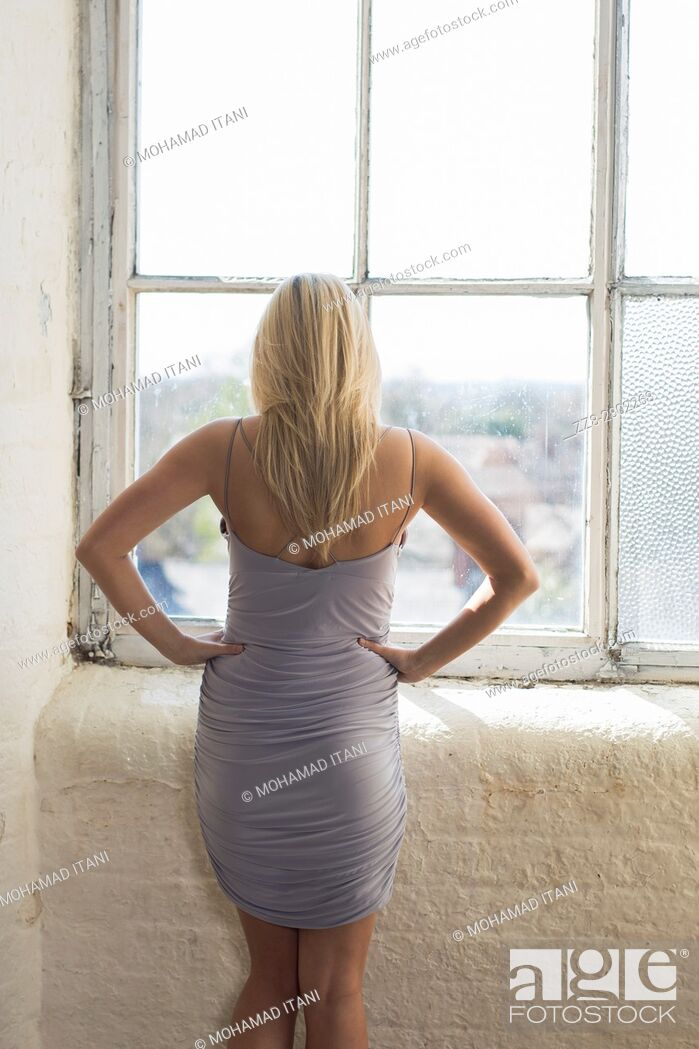 Stock Photo: Rear view of a blond woman standing by the window.