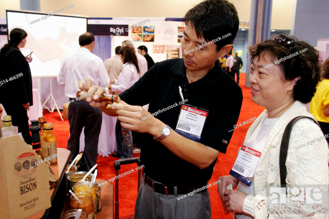 Stock Photo: Convention Center, Americas Food and Beverage Show, Asian couple, hot sauce. Miami Beach. Florida. USA.