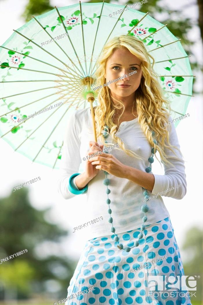 Stock Photo: Young woman holding an umbrella.