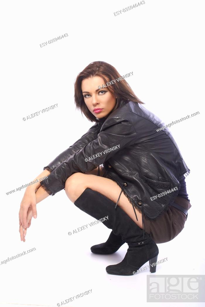 2474ff66c Young dark-haired girl in stylish clothes posing in front of camera ...