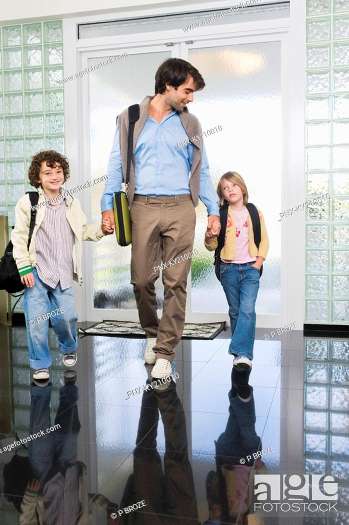Stock Photo: Man entering the house with his children.