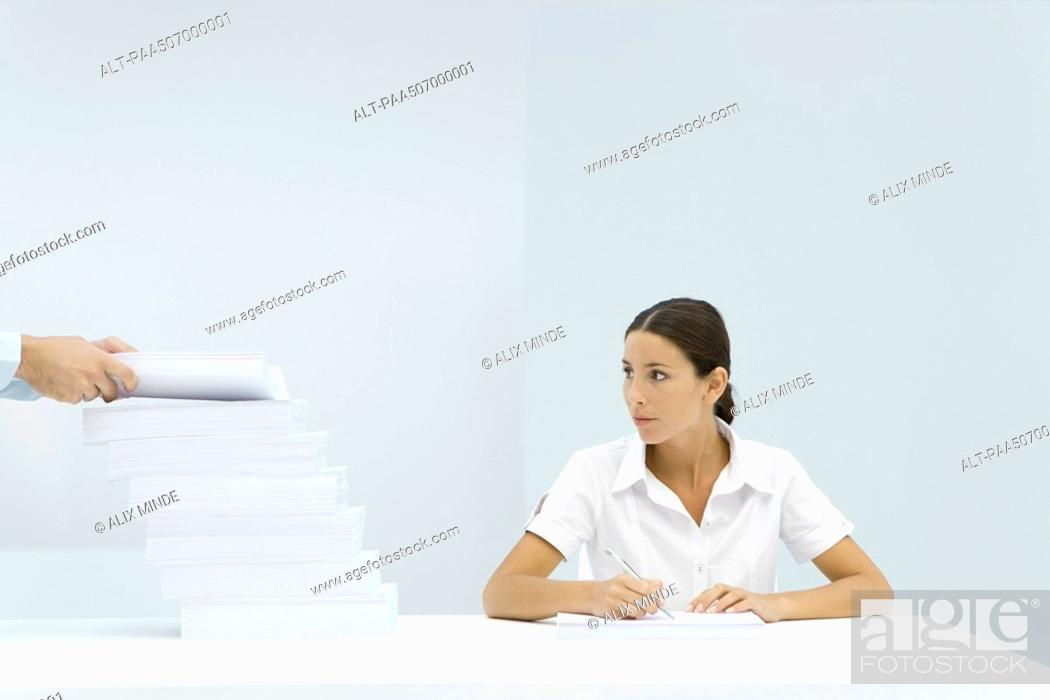 Stock Photo: Woman sitting at table, looking at a staggered stack of paper, man's hands adding paper to the pile.