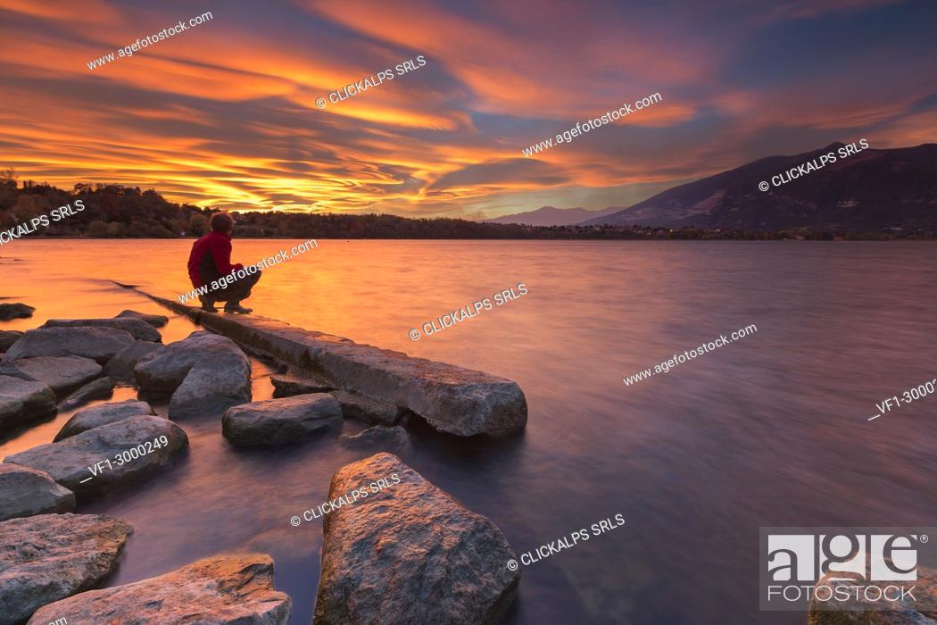 Stock Photo: Man admire an incredible sunset of lenticular clouds on lake Annone, Annone di brianza, Lecco province, Brianza, Lombardy, Italy, Europe.