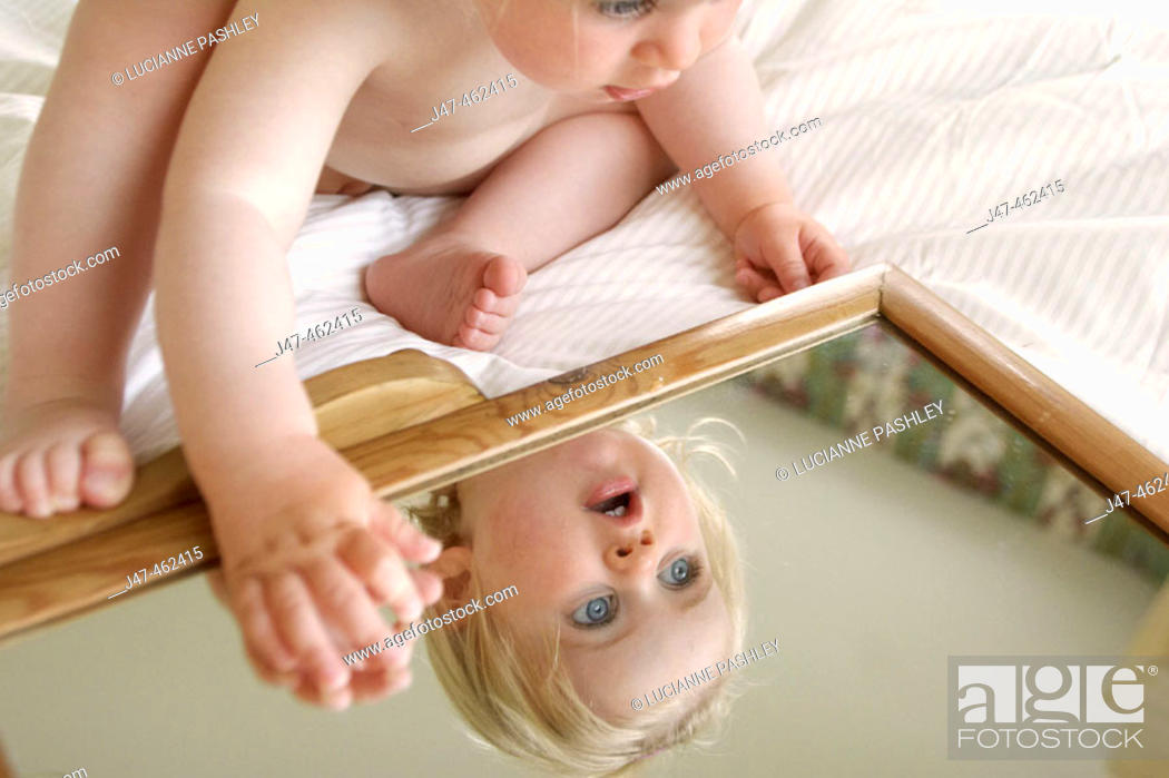 Stock Photo: 18 month old girl sitting leaning over a mirror.