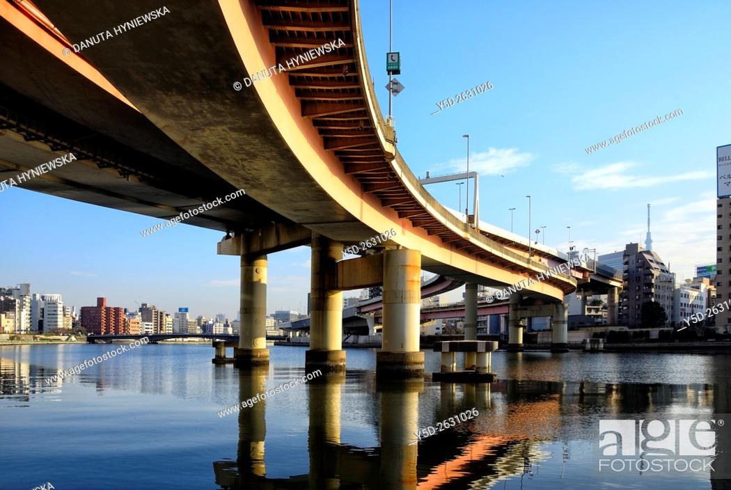 Stock Photo: Urban landscape od Tokyo, Metropolitan Expressways over Sumida river, on left - Chuo , Chuo-ku, on right Sumida-ku and Tokyo Skytree in far background, Tokyo.
