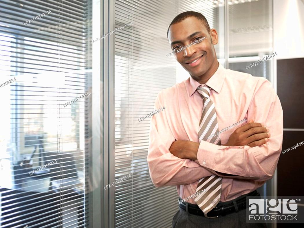 Stock Photo: Businessman by window portrait.